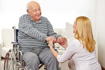 woman holding the hand of the elderly man
