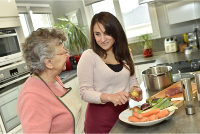 caregiver and elderly woman cooking